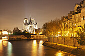 'Lights illuminate the river with an illuminated church in the background; Paris, France'