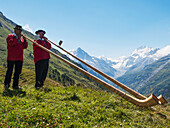 'Two swiss men play alp horns in traditional Valais costume in alpine summer meadow with mountains in the background; Zinal, Switzerland'