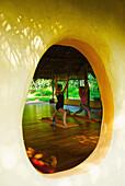 'View through a round window of women doing yoga; Ulpotha, Embogama, Sri Lanka'