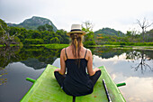'A young woman sits on a green raft in the tranquil water; Ulpotha, Embogama, Sri Lanka'
