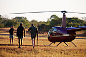 'Veterinarian and pilot boarding a helicopter after Rhinoceros notching, Phinda Private Game Reserve; South Africa'