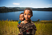 'Young girl with baby on her back in wheat field, Wenchi crater and lake, to the West of Addis Ababa; Ethiopia'