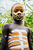 'Surma child with face painted with pigment made from powdered coloured stones, Omo region, Southwest Ethiopia; Kibish, Ethiopia'