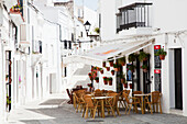 'An outdoor restaurant patio and whitewash buildings; Vejer de la Frontera, Andalusia, Spain'