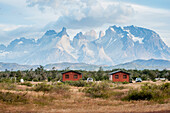 'Two small red cabins in front of rugged mountains; Torres del Pain, Chile'