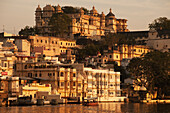 'Buildings glowing in the sunlight of the setting sun along the river; Udaipur, India'