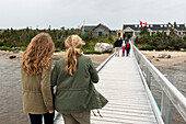 'Tourists walking on dock towards buildings on shore, Gros Morne National Park; Newfoundland, Canada'