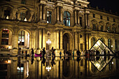 'Tourists are reflected in the pools out the front of The Louvre Museum; Paris, France'