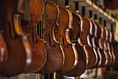 'Repaired violins and violas on racks in The Sound Post repair shop; Toronto, Ontario, Canada'