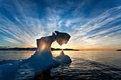 Antarctica, Setting midnight sun lights Iceberg near Palmer Station by Torgersen Island on spring evening