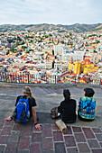 'Three people sit viewing the cityscape of Guanajuato; Guanajuato, Mexico'
