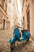 'A blue motor scooter parked outside a residential building; Rome, Lazio, Italy'