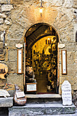 'A retail store with an open arched doorway; Montepulciano, Tuscany, Italy'
