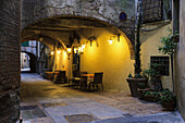 'Seating along a wall illuminated by golden light under a covered walkway; Montepulciano, Tuscany, Italy'