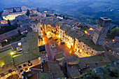 'High angle view of the town with lights illuminating the buildings at dusk; San Gimignano, Tuscany, Italy'
