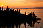 'Sunset glowing orange over Lake Garda with a silhouette of the shoreline; Tirol, Italy'