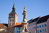 'Statue, clock tower and buildings against a blue sky; Landsberg, Bavaria, Germany'
