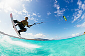 'Professional kiteboarder Andre Philip kitesurfing over the crystal blue waters, Necker Island, British Virgin Islands'