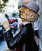 Statue of an elderly man holding a glass of red wine outside a building along a street