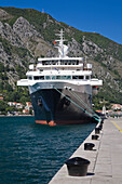 'Dock and moored cruise ship in the port of Kotor with mountain landscape; Kotor, Montenegro'