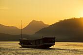 'Boat on the Mekong River at sunset; Luang Prabang, Laos'