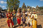 'Traditional dancers in front of 12th century Bayon Temple which is the central temple in Angkor Thom, located north of Angkor Wat; Siem Reap, Cambodia'