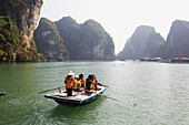 'Local woman rowing boat with tourists to the Vung Vieng Fishing Village in Bai Tu Long Bay, Halong Bay; Vietnam'