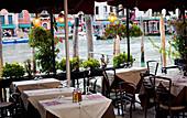 'An outdoor restaurant patio on a canal; Venice, Italy'
