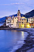 'Buildings illuminated by lights along the water's edge at sunrise; Camogli, Liguria, Italy'