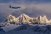 An Alaska Airlines jet on approach to Juneau International Airport passes by Mendenhall Towers, Winter,Tongass National Forest, Juneau, Alaska.