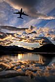 Alaska Airlines jet takes off from Juneau International airport at dawn, Juneau, Alaska.