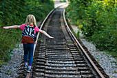 'Girl walking along abandoned railway track, near Clecy; Normandy, France'
