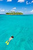 'Woman snorkelling in aqua blue water in front of tropical island, Raiatea, French Polynesia'