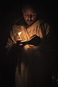 'Ethiopian pilgrim with Bible and candle; Lalibela, Ethiopia'
