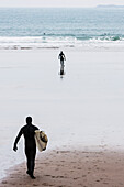 'Dedicated surfers in full cover wetsuit heading out to the chilly winter waters at Whitesands Beach on the Pembrokeshire Coast Path; Pembrokeshire, Wales'