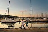 A young girl with a drink in her left hand strolls by the marina along her male partner hand in hand.