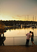 A young girl lip-locks with her male partner, stands by her side by the marina.