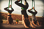 Two young ladies and a young man perform aerial yoga.