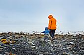 Mother and toddler exploring rocky shoreline on a rainy day in Seward, Alaska.