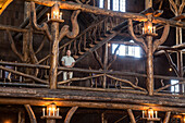 A woman standing next to the intricate logwork inside the Old Faithful Lodge in Yellowstone National Park, Wyoming.