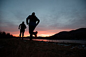 Silhouettes of two runners near Lake Durand in Randolph, New Hampshire while the sun rises on a chilly autumn morning.
