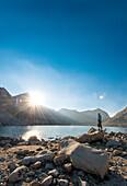 Sunstar and hiker looking over Royce Lakes, High Sierra