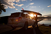A fit female places her stand up paddle board (SUP) on a car at sunset on Whitefish Lake in Whitefish, Montana.