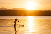 A fit male paddles his stand up paddle board (SUP) along the Hood Canal in the Puget Sound with the Olympic Mountains behind him near Poulsbo, Washington at sunset.