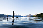 A man and woman stand up paddle boards (SUP) on Lake McDonald at sunset in Glacier National Park near West Glacier, Montana.