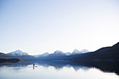 A man stand up paddle boards (SUP) on a calm Lake McDonald at sunrise in Glacier National Park near West Glacier, Montana.