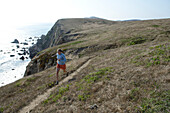 A woman enjoys the trial with a view at Point Reyes National Seashore, California.