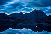 An illuminated tent reflected in a lake in front of Jagged peak deep in the Weminuche wilderness near Silverton Colorado.
