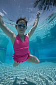 a girl floating toward camera underwater in pool wearing a pink swimsuit and goggles