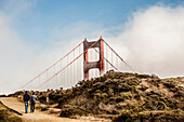 The Golden Gate surrounded by fog, partially visible over a hill where two guys are walking.